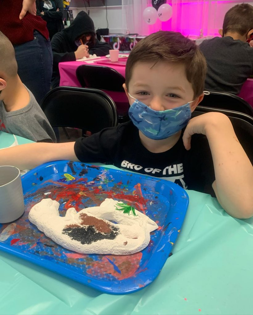 Happy boy in mask panting dinosaur plaster piece