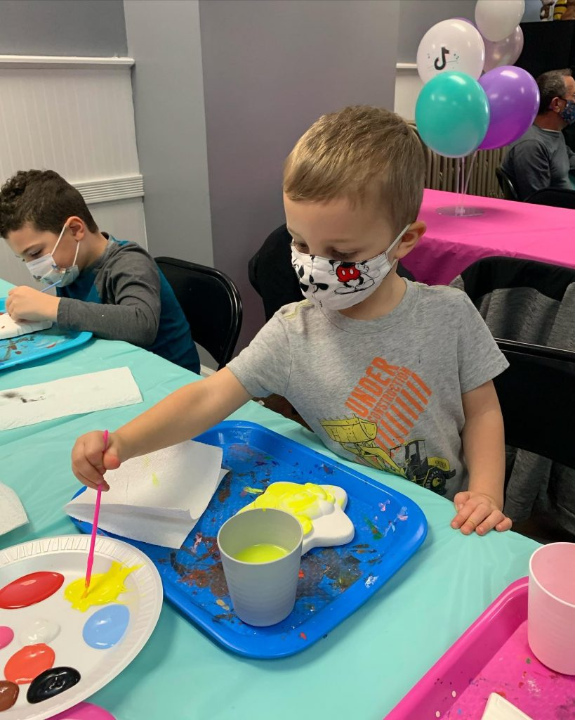 Boy in mask painting during plaster paint party