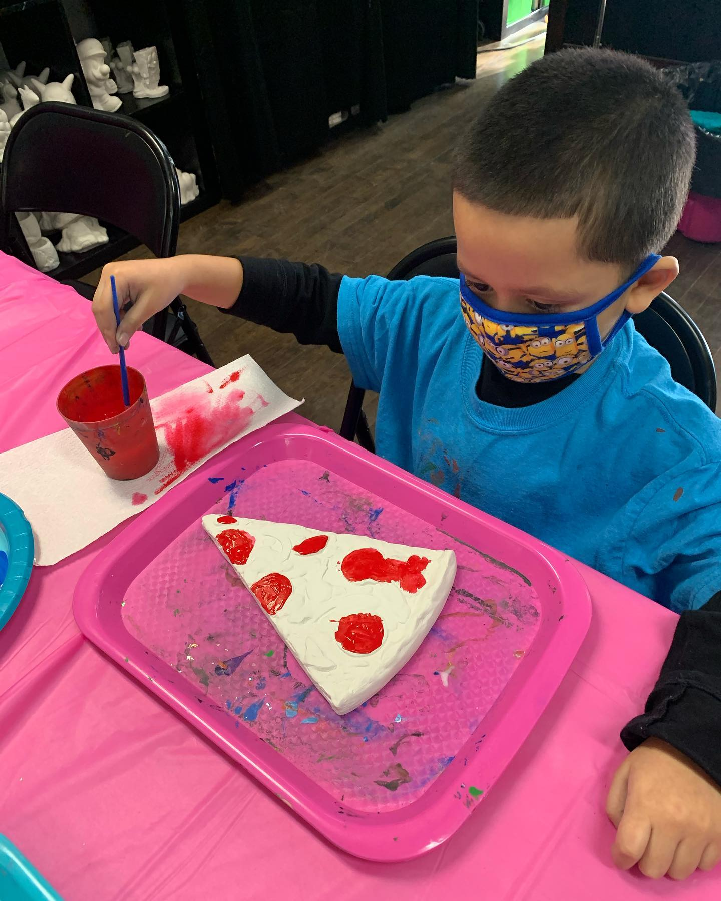 Boy in mask painting pizza plaster piece