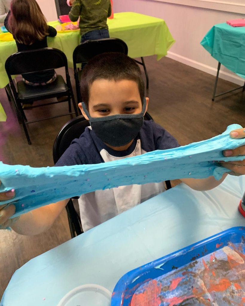 Happy boy in mask making slime