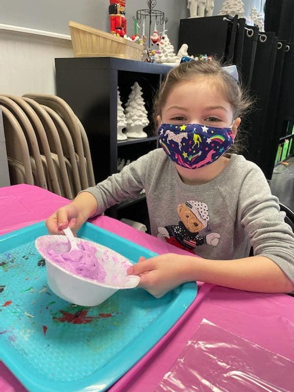 Happy girl in mask making slime