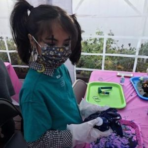 Girl making tie dye in outdoor tent