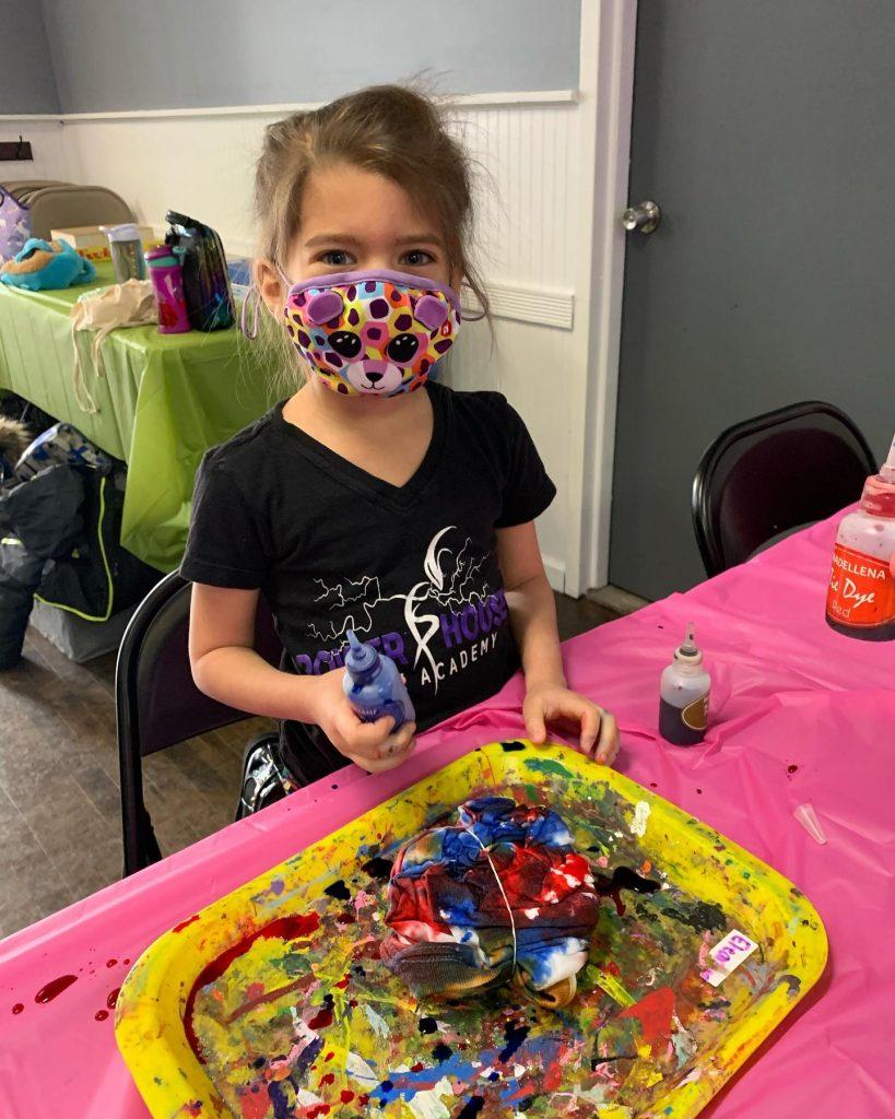 Cute girl in mask making tie dye