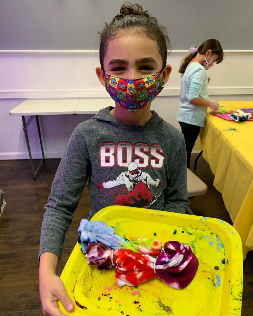 Child in mask with tie dye shirt