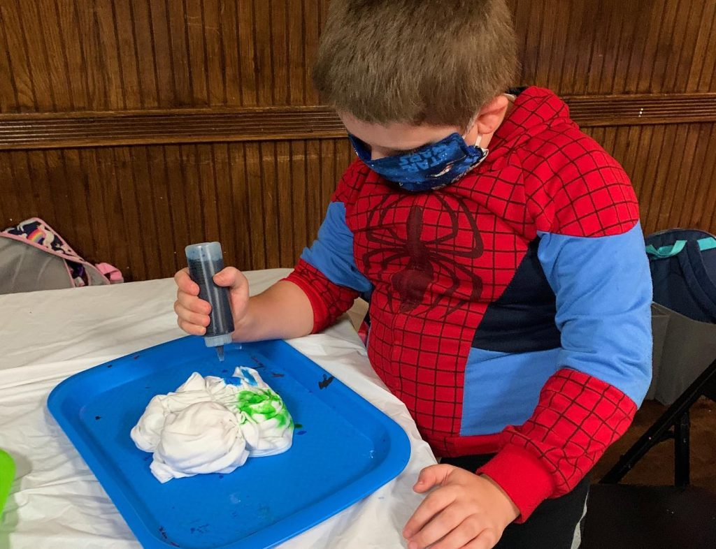 Boy in Spiderman costume making tie dye shirt
