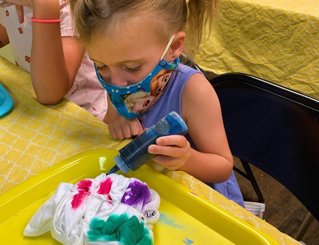 Cute girl in Frozen mask making tie dye