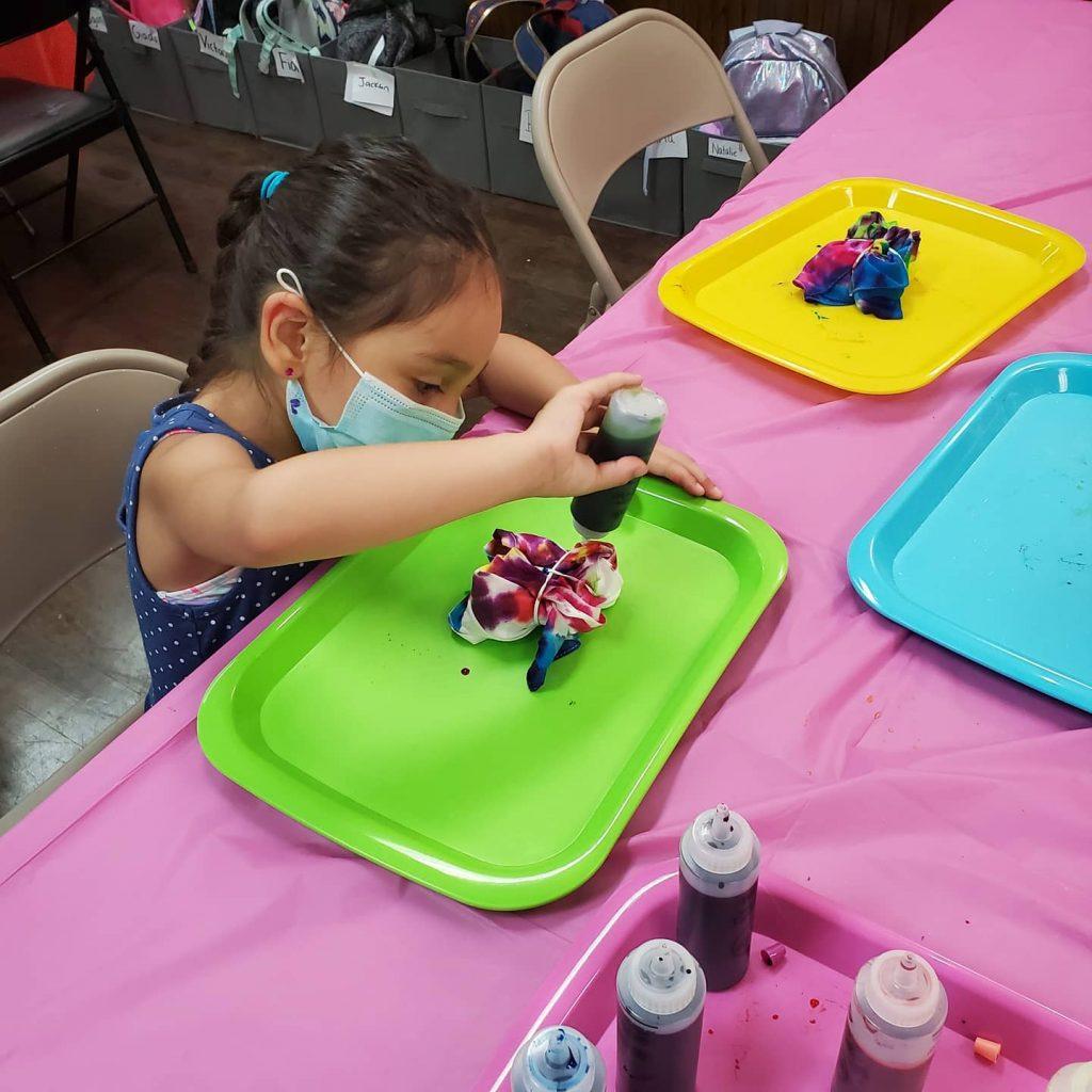 Girl in mask making tie dye shirt