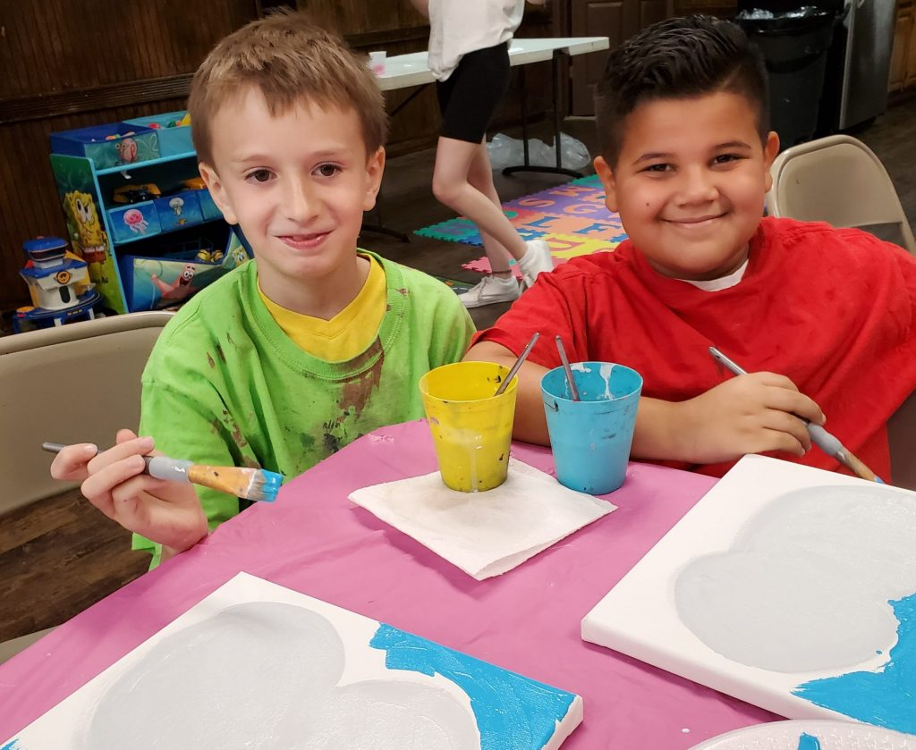 Boys painting during paint party