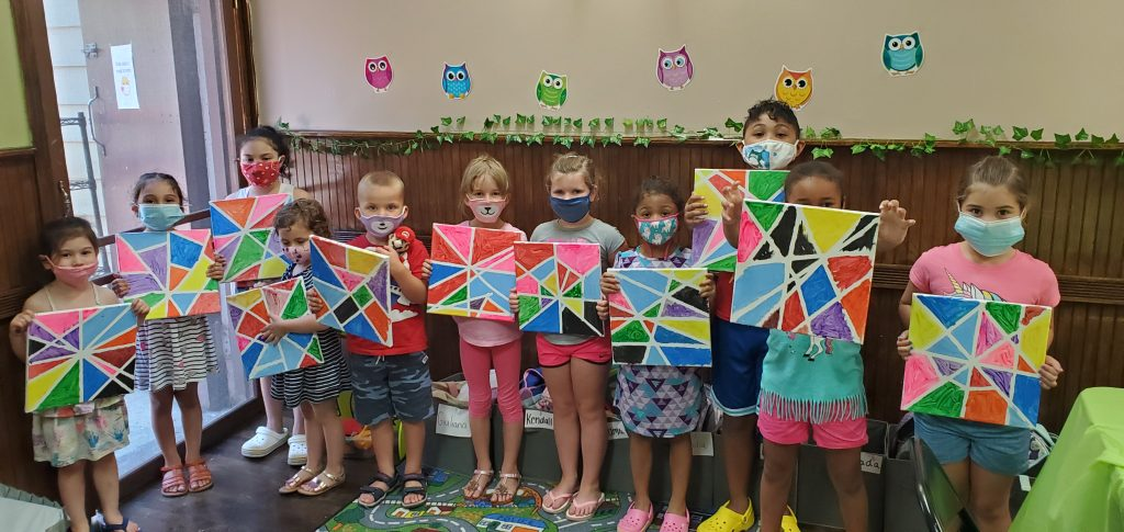 Children in masks showing mosaic themed canvas paintings