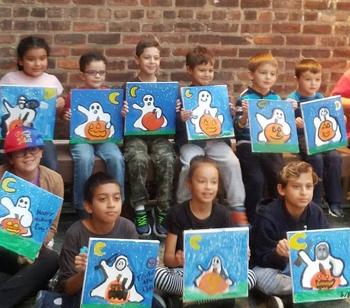 Children showing Halloween canvas paintings