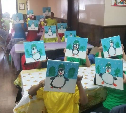 School kids showing penguin themed canvas paintings