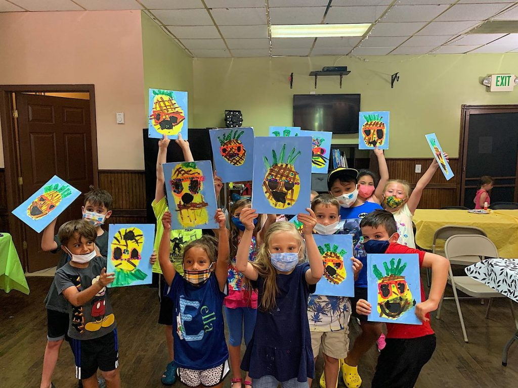 Kids in masks showing canvas painting of pineapple